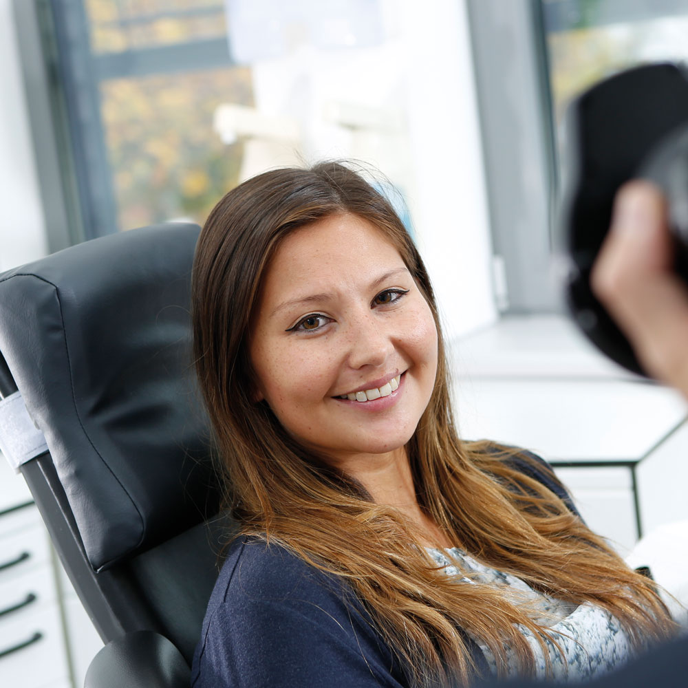 Frau freut sich über weiße Zähne nach Zahnbleaching Langenhagen