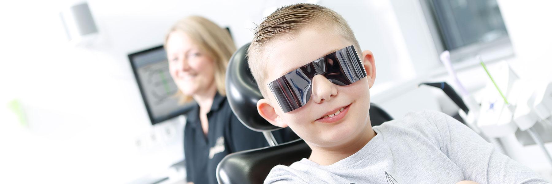 Junge trägt Schutzbrille bei Laser Zahnarzt Langenhagen